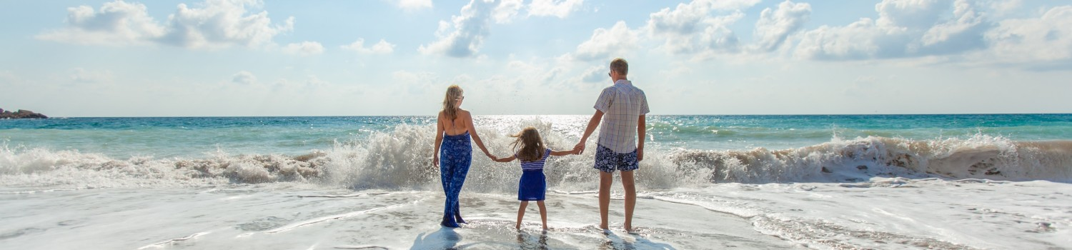 Family on Mount maunganui beach with a wave crashing in front of them cr